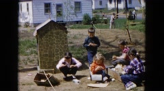 1955: children gathering items and playing near a home with adults  Stock Footage