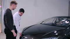 Manager demonstrate the trunk of car to customer Stock Footage