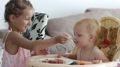 Children eating, little girl is feeding her little sister Stock Footage