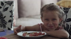 Children and nutrition, little girl is eating in home kitchen, cute baby face Stock Footage