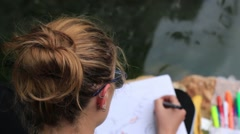 White Female Blond Artist Wearing Glasses, Drawing on the River Multi Color Pens Stock Footage