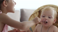 Children and nutrition, little girl is feeding her little sister Stock Footage