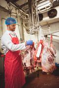 Butcher sticking barcode stickers on red meat in storage room Stock Photos
