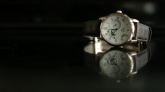 Wide shot of a White Wrist Watch on a dark reflective surface Stock Footage
