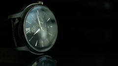Medium shot of a tilted Black Wrist Watch on a dark reflective surface Stock Footage