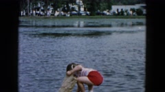 1955: two girls along the shore of a pond, playing in the water HICKSVILLE Stock Footage