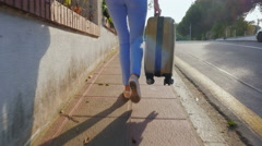Steadicam shot: Woman tourist walking on the road with a travel bag. Spain Stock Footage
