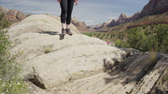 Wide panning low angle view of woman balancing on boulder / Zion National Park, Stock Footage