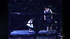 1955: a woman and a little girl in a dress standing on a wooden platform or dock Stock Footage