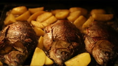 Roasted carp with potatoes in the oven Stock Footage