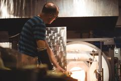 Glassblower heating a glass in furnace Stock Photos