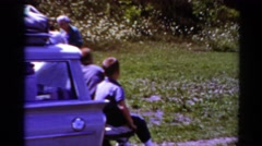 1964: little boys sit on the tailgate of a station wagon as people walk, talk Stock Footage