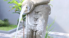 Asian balinese stone statue of woman with jug. The water flowing from jug. Stock Footage