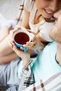 Amorous young couple holding cup of hot tea Stock Photos