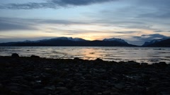 Golden sunset over new snow mountain range and birds in fjord water Stock Footage