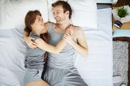 Happy couple talking in bed in the morning Stock Photos