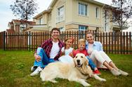 Family of new settlers sitting on grass with their house behind Stock Photos