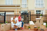 Two kids sitting in armchair in the front yard with packed things near by Stock Photos