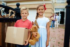 Sister and brother helping their parents to carry things while moving for new ho Stock Photos