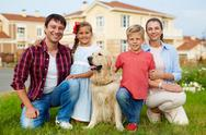 Happy family with dog looking at camera outdoors Stock Photos
