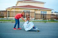 Ecstatic girl sitting on skateboard while her brother pushing it Stock Photos