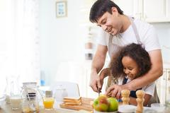 Young father showing his daughter how to cut bread Stock Photos