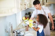 Little girl washing dishes with her father near by Stock Photos