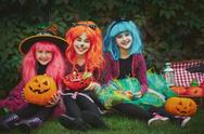 Three witches in wigs sitting on grass Stock Photos