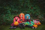 Little girls in Halloween attire looking at camera outdoors Stock Photos