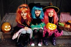 Row of cute girls wearing hats and Halloween attire Stock Photos