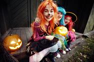 Girls in costumes and wigs sitting outdoors Stock Photos