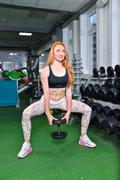 Sexy young girl doing squats exercises with dumbbells. Fitness woman workout in Stock Photos