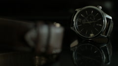 Medium shot of a Black Wrist Watch with wrist band on a dark reflective surface Stock Footage
