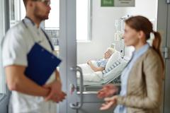 Senior patient lying in bed in hospital ward while her relative talking to docto Stock Photos