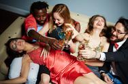Flutes with champagne in hands of ecstatic friends during toast Stock Photos