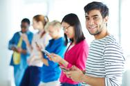 Young guy with cellphone looking at camera with his groupmates on background Stock Photos