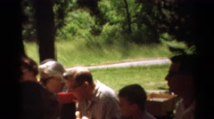 1964: friends and family gather at an outdoor picnic at a table in the shade Stock Footage