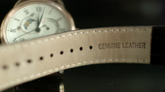 A close up of a golden Wrist Watch with wrist band against dark background Stock Footage