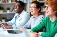 Happy intercultural students looking at spokesperson during presentation Stock Photos