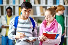 Students checking words in dictionary at break Stock Photos