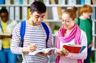 Friendly teens reading something in book or dictionary Stock Photos