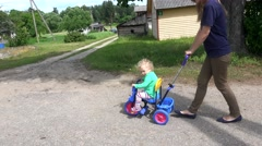 Young woman mother pushing blond toddler girl on small tricycle Stock Footage