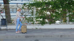 Steadicam shot: Young woman with suitcase on the road wheels are on the pavement Stock Footage