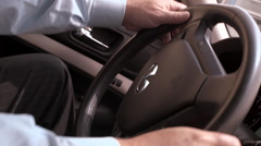 Man driving a car through city with hands on the wheel Stock Footage
