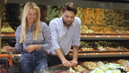 Couple choose bell peppers at the supermarket Stock Footage