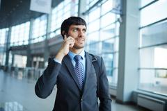 Young man speaking on the phone on the move Stock Photos