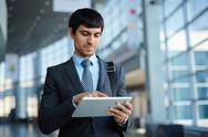 Businessman browsing in his touchpad in office center Stock Photos