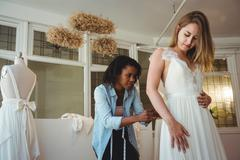 Woman trying on wedding dress with the assistance of fashion designer Stock Photos