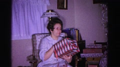 1967: woman sitting in rocking chair, unwrapping gift HAGERSTOWN, MARYLAND Stock Footage