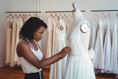 Female fashion designer adjusting the dress on mannequin Stock Photos